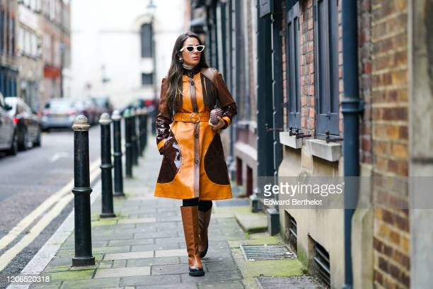 Nurce Erben wears sunglasses, an orange and brown leather long coat, a belt, a clutch, brown leather high boots, during London Fashion Week Fall...