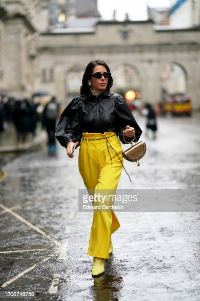 Nurce Erben wears sunglasses, earrings, a black leather top with puff sleeves, yellow pants, a Chloe semi-circular bag, yellow pointy boots, during...