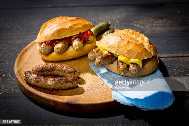 nuremberg grilled sausage, wheat roll with mustard ketchup and gherkin on wooden plate - sausage bap stock photos and pictures