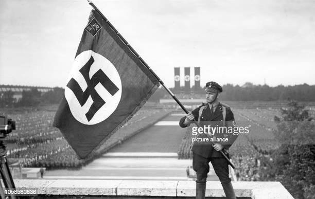 Nuremberg Rally 1933 in Nuremberg Germany A member of the SS holds up a flag for the camera during the commemoration of the dead at the Nazi party...