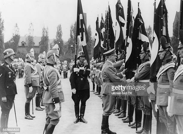 Nuremberg Rally 1937 Adolf Hitler consecrating the flags of the German police with the Nazi ceremonial flag the socalled 'blood flag' far left the...