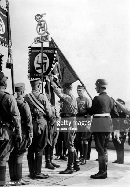 Nuremberg Rally 1938 in Nuremberg, Germany - The new standards are consecrated by Adolf Hitler with the 'Blood Flag', behind Hitler the standard...