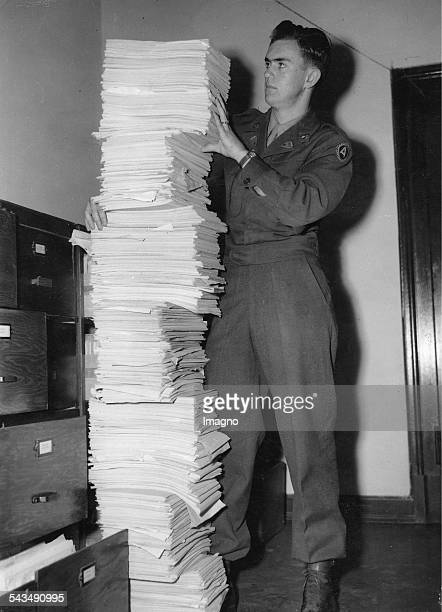 Nuremberg Trials. US Soldier Herbert Boe from the translation division holding a pile of transcripts representing a little part of the evidence for...