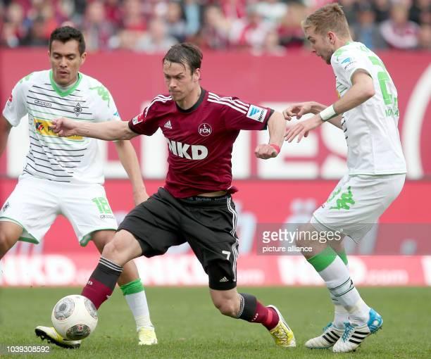 Nuremberg's Markus Feulner vies for the ball with Gladbach's Juan Arangotwitter and during Christoph Kramer during the Bundesliga soccer match...