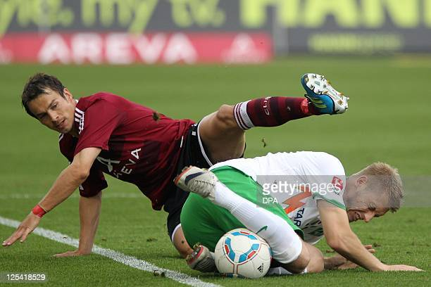 DURING THE MATCH AND PROHIBITS MOBILE USE Nuremberg's midfielder Markus Feulner and Werder Bremen's striker Aaron Hunt fight for the ball during the...