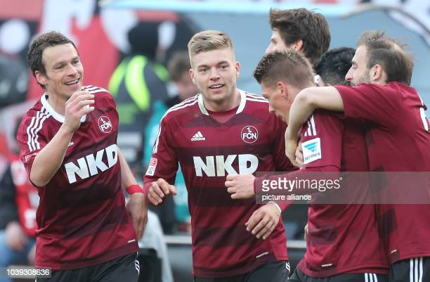 Nuremberg's Mike Frantz cheers with Markus Feulner and Alexander Esswein during the German Bundesliga soccer match between 1 FC Nuremberg and FC...