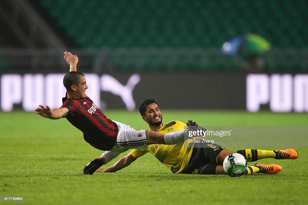 Nuri Sahin of Borussia Dortmund competes for the ball with Jose Mauri of AC Milan during the 2017 International Champions Cup football match between AC milan and Borussia Dortmund at University Town Sports Centre Stadium on July 18, 2017 in Guangzhou, China.