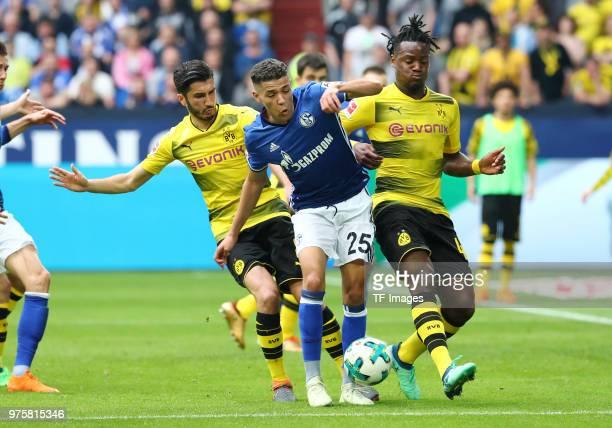 Nuri Sahin of Dortmund and Amine Harit of Schalke Michy Batshuayi of Dortmund battle for the ball during the Bundesliga match between FC Schalke 04...