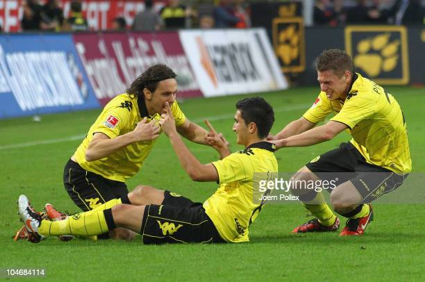 Nuri Sahin of Dortmund celebrates with his team mates Neven Subotic and Lukasz Piszczek after scoring his team's second goal during the Bundesliga...