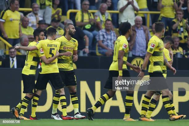 Nuri Sahin of Dortmund is congratulated by Marc Bartra of Dortmund and his team mates after he scored to make it 20 during the Bundesliga match...