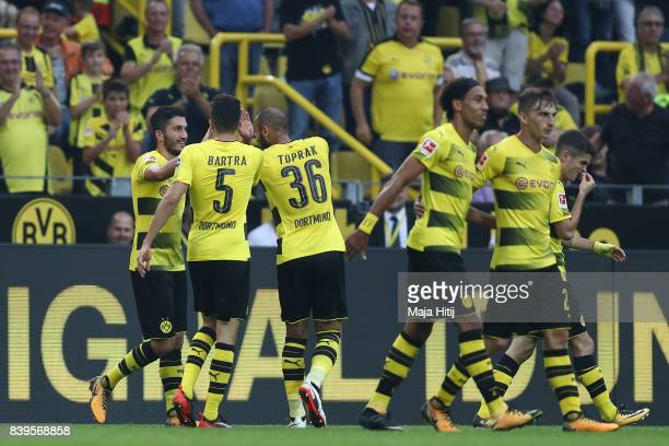 Nuri Sahin of Dortmund is congratulated by Marc Bartra of Dortmund and Oemer Toprak of Dortmund and his team mates after he scored to make it 20...