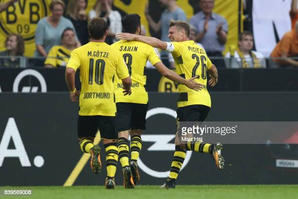 Nuri Sahin of Dortmund is congratulated by Mario Goetze of Dortmund and Lukasz Piszczek of Dortmund after he scored to make it 2:0 during the...