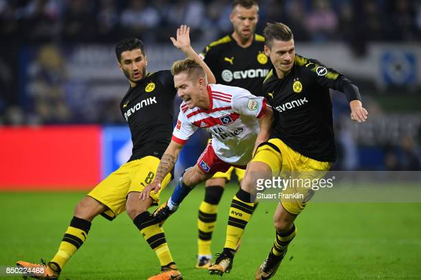Nuri Sahin of Dortmund Lewis Holtby of Hamburg and Lukasz Piszczek of Dortmund fight for the ball during the Bundesliga match between Hamburger SV...