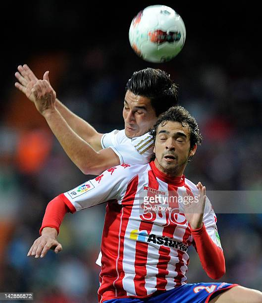 Nuri Sahin of Real Madrid CF goes for a high ball against Alberto Tomas Botia of Real Sporting de Gijon during the La Liga match between Real Madrid...
