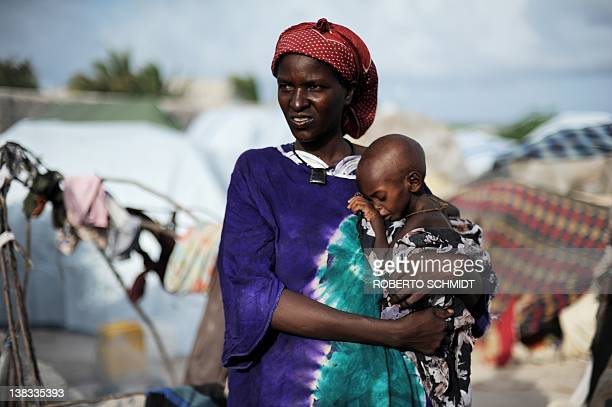 Nuro Mo'alim holds her measles stricken twoyearold boy Medhi in her arms as she stands amids makeshift shelters at a camp for Internally Displaced...