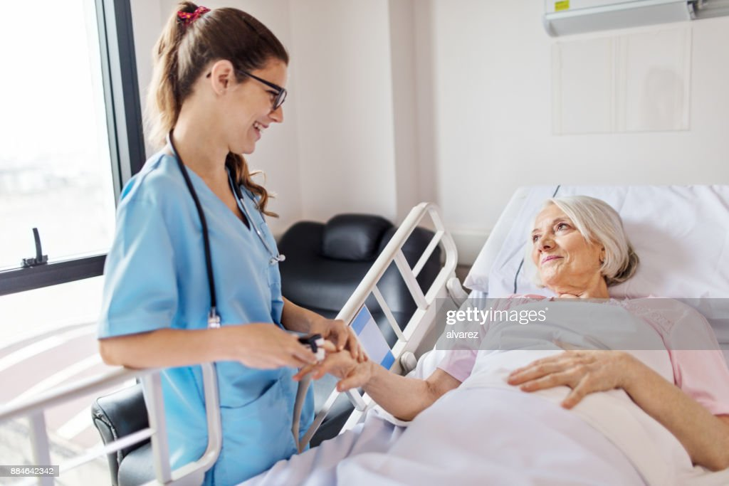 Nurse adjusting oxymeter on senior woman's finger : Stock Photo