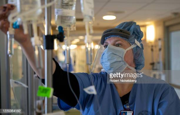 Nurse adjusts intravenous drug dosages being given to a COVID-19 patient on the Intensive Care Unit floor at the Veterans Affairs Medical Center on...