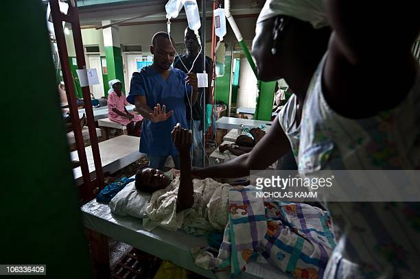 A nurse adjusts the IV drip of a woman suffering from cholera at the Charles Colimon hospital in Petite Riviere on the Artibonite river believed to...