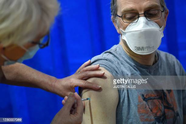 Nurse administers the Pfizer-BioNTech COVID-19 vaccine to a man at a health centre in Cardiff, South Wales' on December 8, 2020. - Britain on...