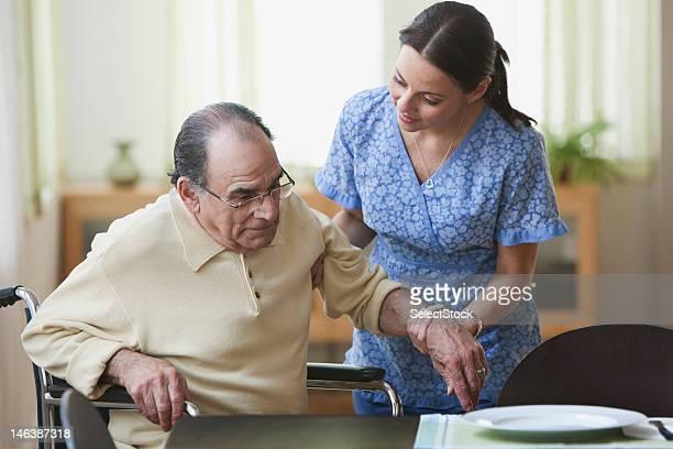 Krankenschwester fördert ein älterer Mann stand vom Rollstuhl