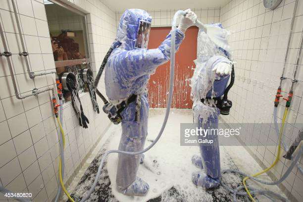 A nurse and a doctor for tropical medicine wearing isolation suits demonstrate the decontamination procedure as part of ebola treatment capability at...