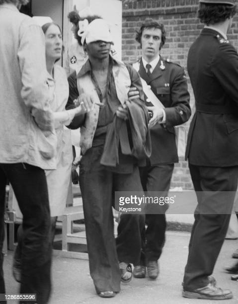 Nurse and a member of the St John Ambulance assist a young man injured in the riots which marred the close of the Notting Hill Carnival, held across...
