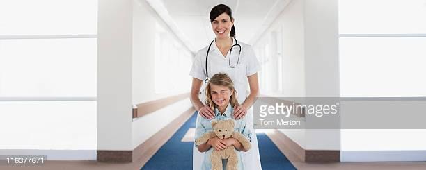 Enfermeira e criança doente com Urso de Pelúcia no corredor de hospital