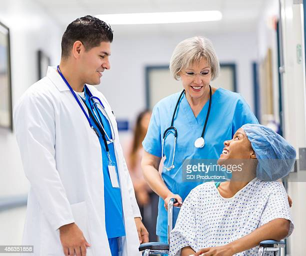 nurse and docgor talking to happy hospital patient after surgery - medical procedure stock pictures, royalty-free photos & images