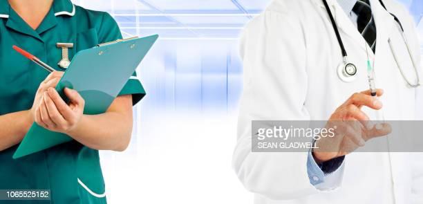 Nurse and doctor holding syringe