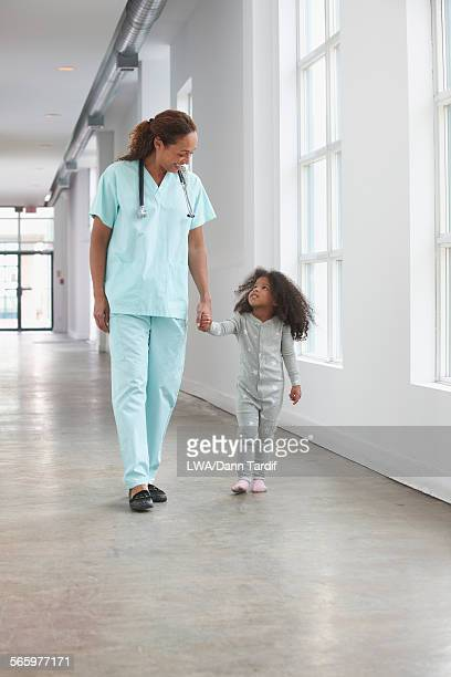 Nurse and girl holding hands in hallway