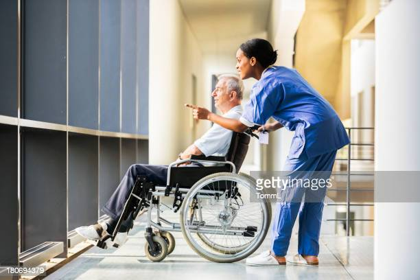 nurse and mature man in wheelchair - a sense of home stock photos and pictures