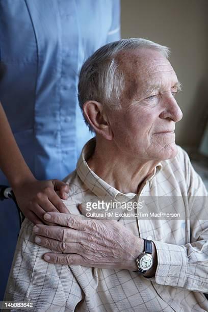 Nurse and older man holding hands