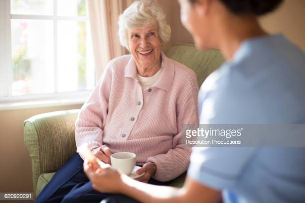 nurse and patient drinking tea on sofa - home carer - fotografias e filmes do acervo