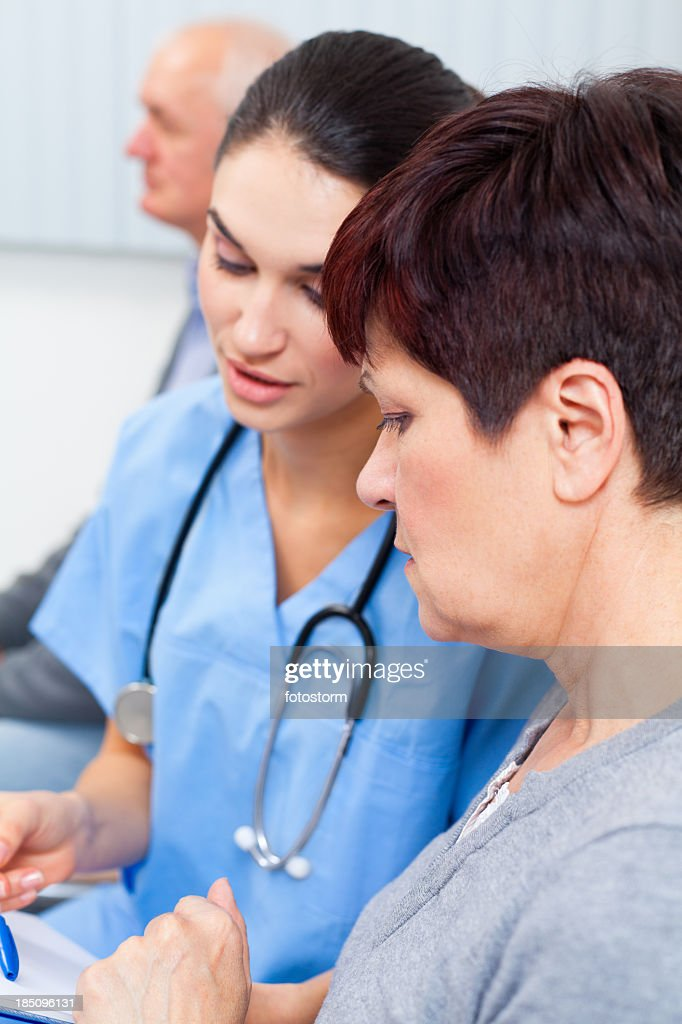 Nurse and patient examining medical records : Stock Photo