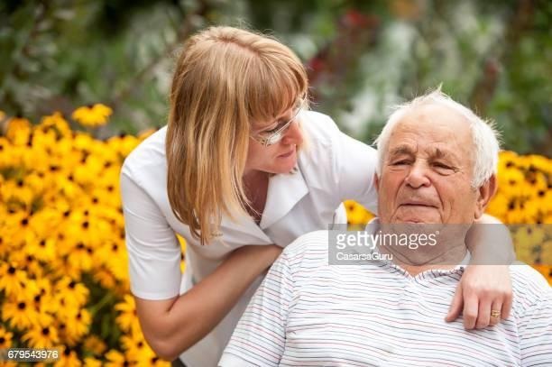 Krankenschwester und Senior Mann im Rollstuhl entspannen im Hinterhof der Ruhestandsgemeinschaft