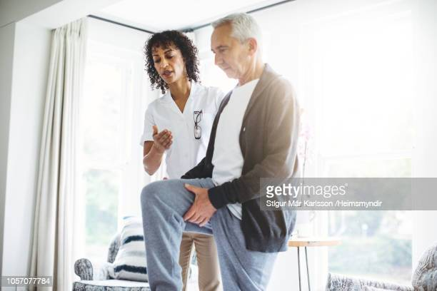 nurse and senior patient exercising at home - physical therapy stock pictures, royalty-free photos & images