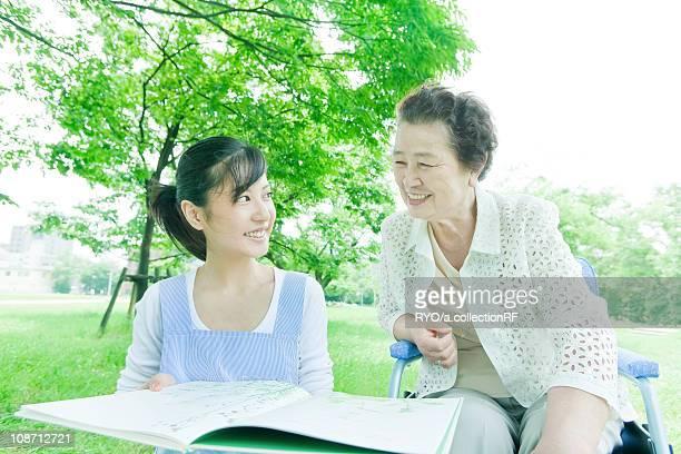 Nurse and senior woman on wheelchair reading a book