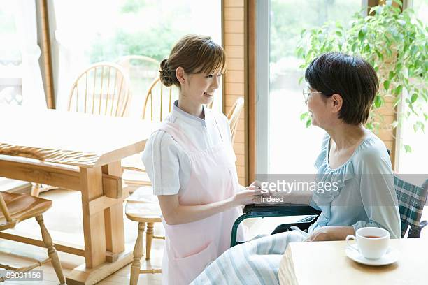 Nurse and senior woman smiling face to face