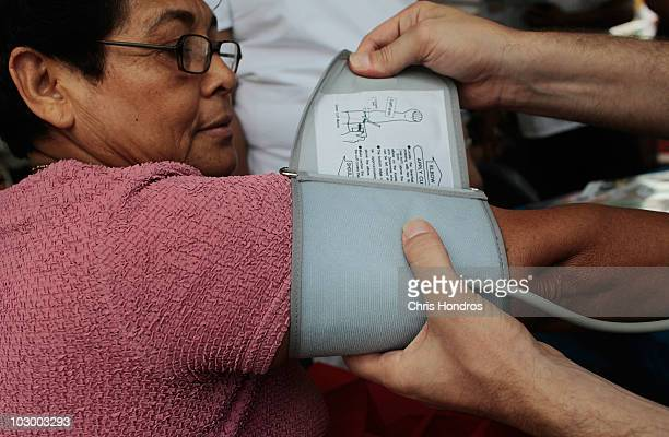 A nurse applies a bloodpresssure cuff to bodega worker during a free healthscreening clinic for New York bodega convenience store workers July 20...