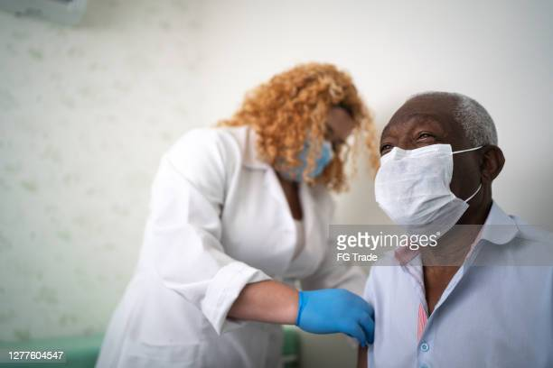 nurse applying vaccine on patient's arm - patient safety stock pictures, royalty-free photos & images