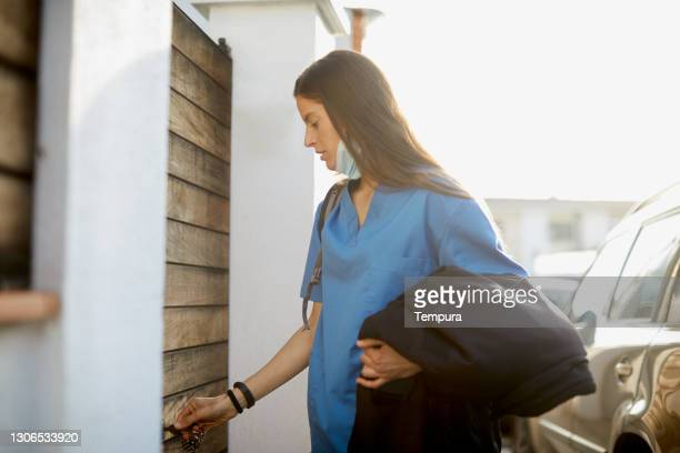 a nurse arriving back home and opening the front door. - arrival stock pictures, royalty-free photos & images