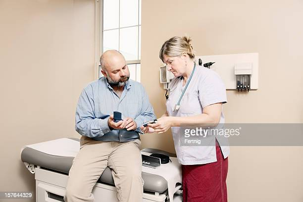 Nurse assisting diabetic patient with equipment