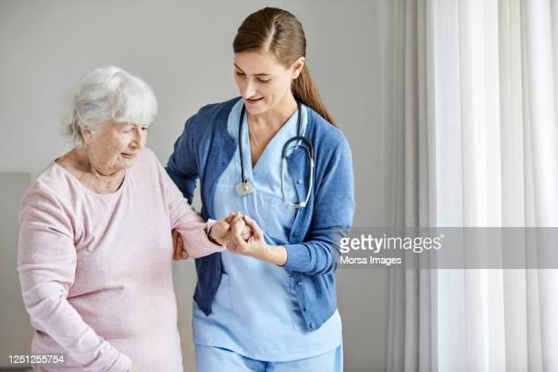nurse assisting elderly female in walking at home - fürsorglichkeit stock-fotos und bilder