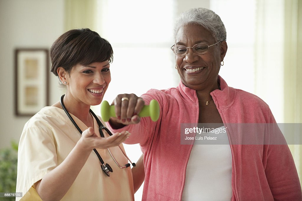 Nurse assisting elderly female patient with physic : Stock Photo
