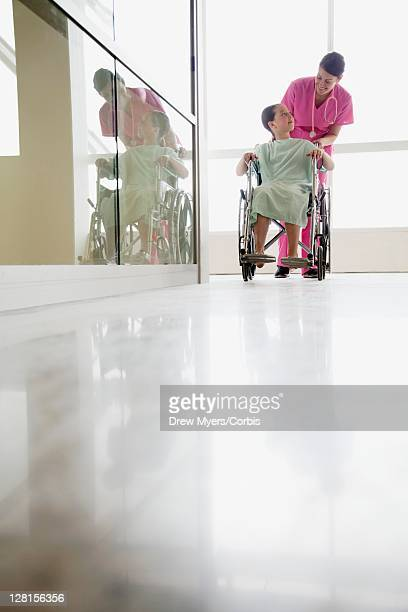 Nurse assisting girl (10-12) on wheelchair in hospital corridor