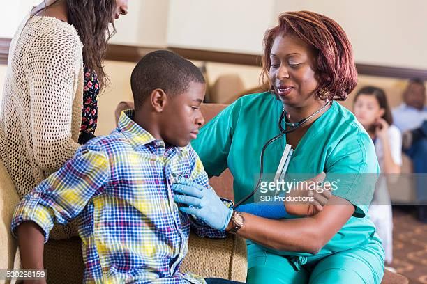 Nurse assisting injured preteen boy in hospital waiting room