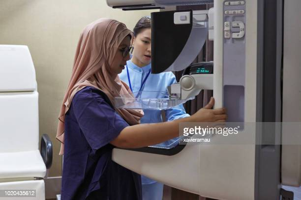 nurse assisting patient during mammography exam - mammogram stock pictures, royalty-free photos & images