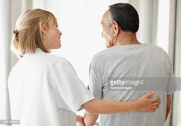 nurse assisting patient with a walker - seulement des adultes photos et images de collection