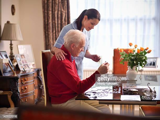 Nurse assisting senior man to complete jigsaw puzzle