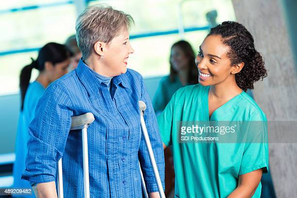 nurse assisting senior patient during physical therapy appointment - crutch stock photos and pictures
